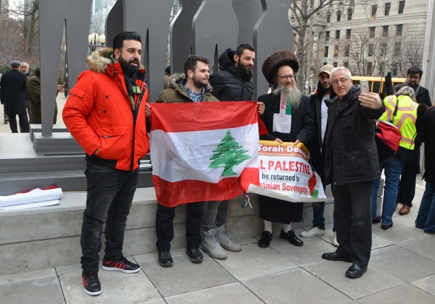 protest at Trumps decision to recognize Jerusalem as capital of Israel, University Ave. A group is gathered around a man holding a Lebanese flag.