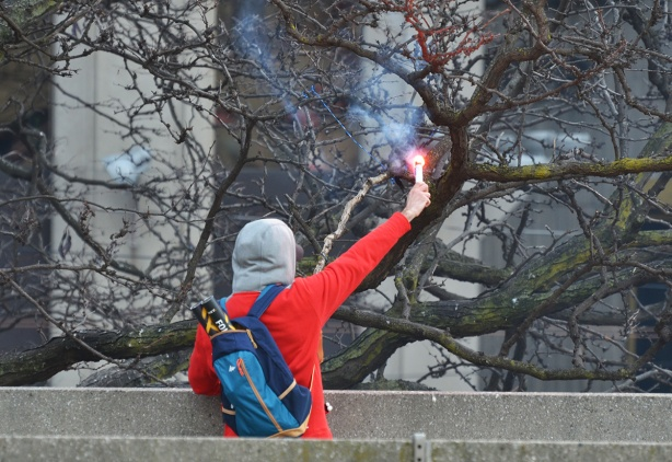 from the back, a youngman holds out a flare
