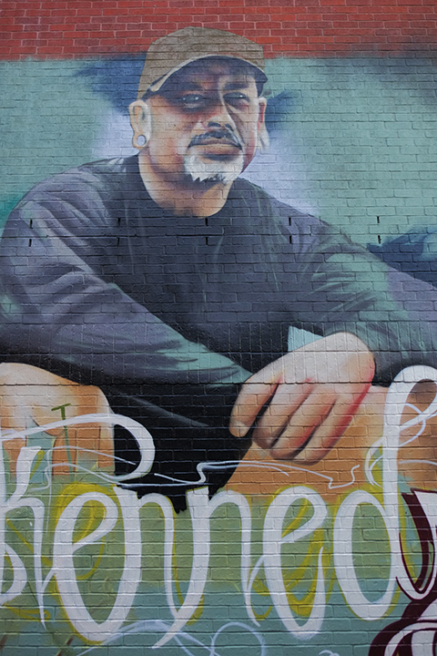 middle section of a partially painted mural, in honour of Mike Kennedy, his portrait.