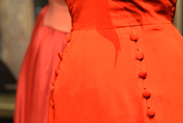 part of an orange dress with cloth covered orange buttons on both the front and side