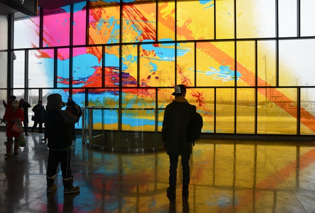 people standing and looking at a large painted window, abstract in yellows, turquoise andpink, large window, at subway station, sunlight outside