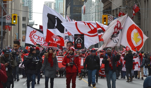 Toronto FC parade, people dressed in red and white, photographers walk in a line in front of one of the banners in the tfc parade up Bay street to celebrate thesoccerteam's championship win