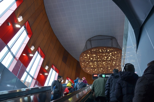 interior of Pioneer Village subway station, top of one of the escalators, vertical windows looking outside, some red glass as accents, a large light artwork on the ceiling, people on the escalators