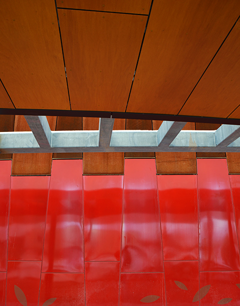 abstract of the exterior walls of Pioneer Village subway station, red panels with wood roof and grey steel beams