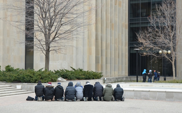 group of men in a line, kneeling, praying, outside,