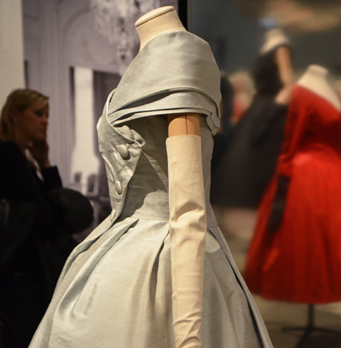 pale blue grey silk Christian Dior dress in the background, a red and a black dress are in the background, ROM exhibit,