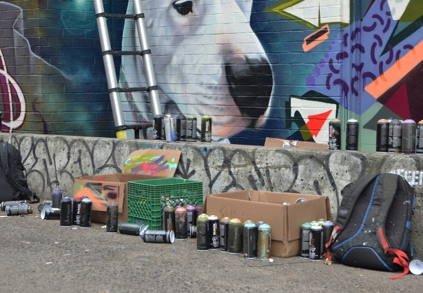 mural, white dog, with a row of spray paint cans in front