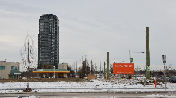 suburbia - empty field with orange sign that says Subway parking. one tall building, a gas station, a street,