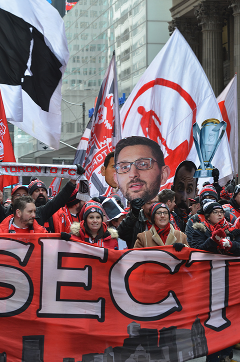 Toronto FC parade, people dressed in red and white, a group holding a banner as they walk