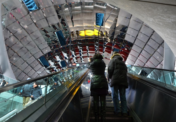 reflective ceiling of Vaughan subway station, with people going up the escalator towards it, taking pictures.