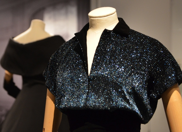 two headless mannequins with black dresses, upper parts only are shown, part of a ROyal Ontario museum exhibit dress in foreground has iridescent beads sewn on it