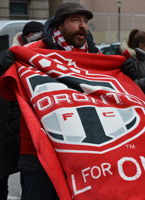 Toronto FC parade, people dressed in red and white, a man wearing a large tfc team flag