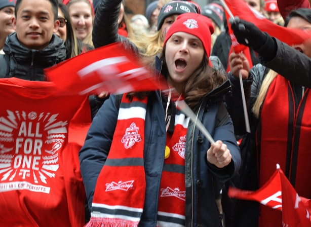 Toronto FC parade, people dressed in red and white, wearing red and white toque and scarf and waving a tfc team flag