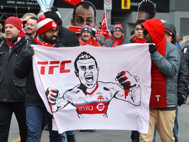 Toronto FC parade, people dressed in red and white, men holding a banner