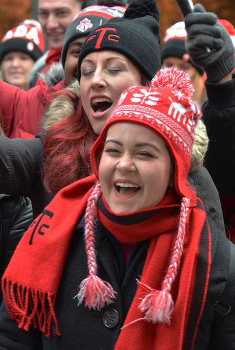 women in a crowd of Toronto FC supporters in a parade