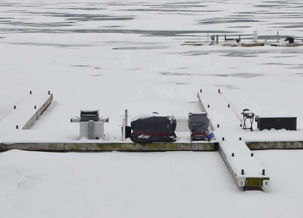 barbecues under tarps on snow covered docks in partially frozen harbour