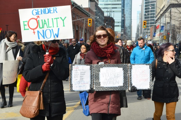 Toronto womens march and protest, a woman with a sign that says gender equality now, and a woman with a sign that says end violence against women along with the names of women who have been killed by their partners.