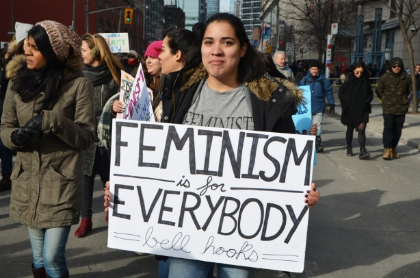 Toronto womens march and protest, a young woman with a sign that says feminism is for everybody