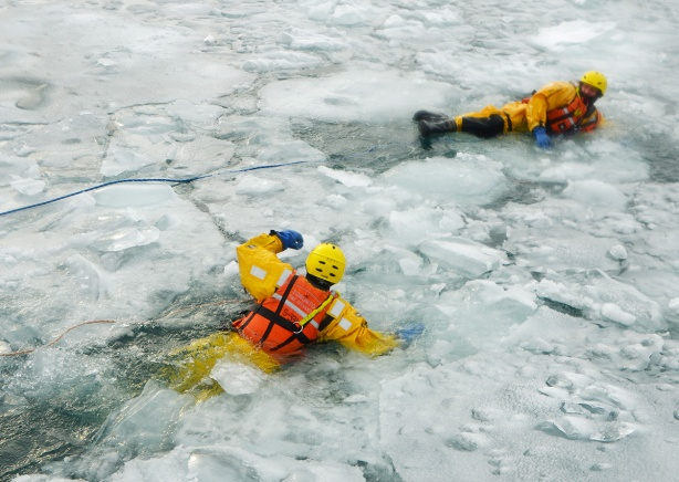 two Toronto firemen in their yellow cold water suits, life jackets on, and tethered to ropes, practicing breaking through ice and then recovering by makng their way to stronger ice, practising ice rescues