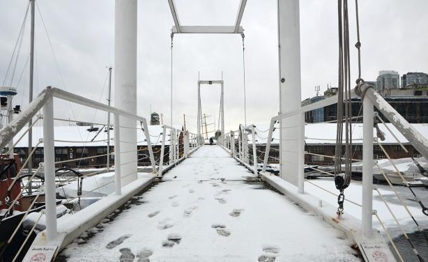 a few footprints in the snow on a bridge