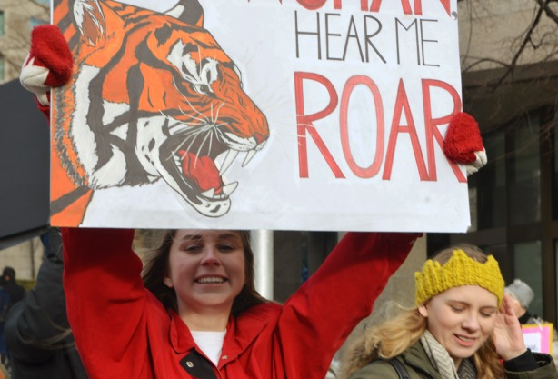Toronto womens march and protest, a smiling woman with a placard that reads hear me roar, along with a picture of a tiger