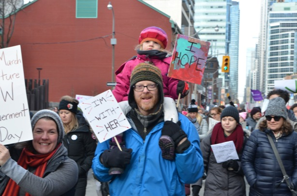 little girl on father's shoulders in Toronto womens march on Bay street, holding sign that says I hope