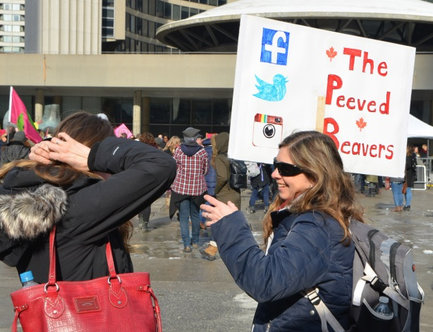 Womens March, Nathan Phillips square, two women talking, one is holding a sign that says the Peeved Beaver
