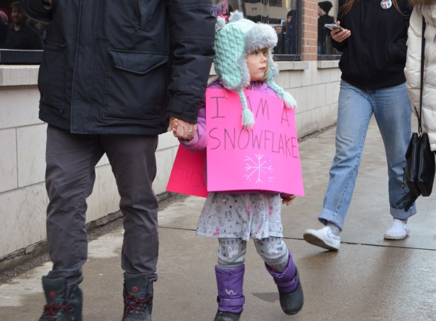 Womens march, protest parade - a girl walking with her father, she has a pink sign that says I am a snowflake