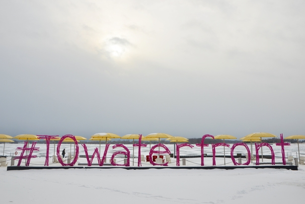 H 2 O park on Toronto's waterfront with yellow umbrellas over white Muskoka chairs on what is a beach in the summer but is covered with snow in the picture. A pink sign that says #TOwaterfront made of pink wood that is supposed to look like pieces of driftwood