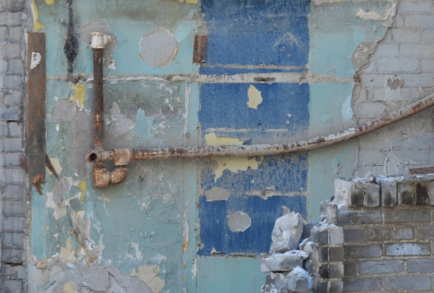 old metal water pipes exposed on green and blue interior wall when building being demolished