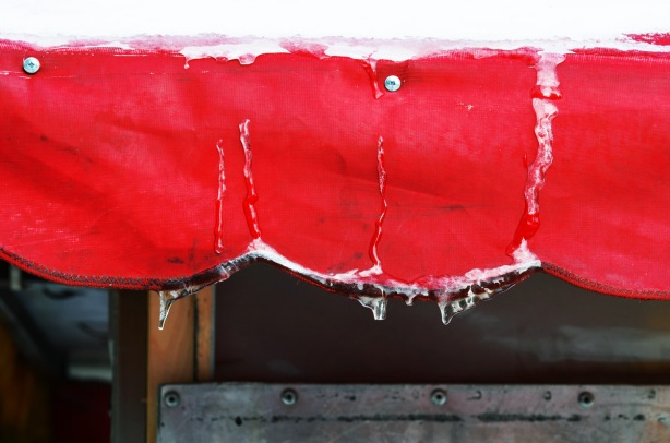 scalloped edged awning, in winter, with snow on the top and some froze drips of water and icicles