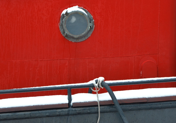 close up of porthole and red wall on boat in the harbour, railing and rope knotted, both with snow on them