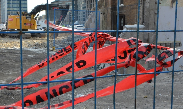 red plastic danger tape blows in the wind. one end is tied to a blue fence and one strand is also tied to a building being demolished