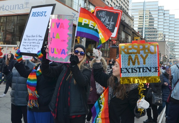 Womens march, protest parade - young women with signs and rainbow peace flags