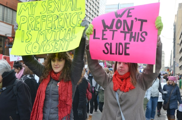 two women holding up signs, a pink one that says we won't let this one slide and a yellow sign that says my sexual preference is mutual consent
