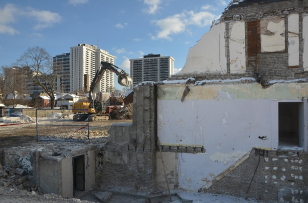 remains of an old building being torn down in the foreground, a front end loader in the middle, and apartment buildings in the background.