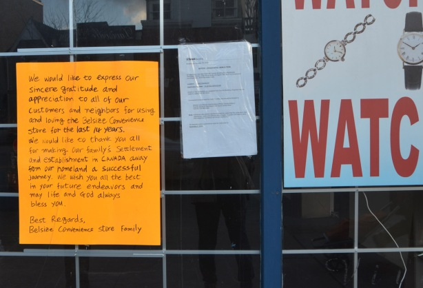 signs in the window of a store that has just closed down. one is a permit to demolish the building and the other is a hand written sign on orange paper that is a thank you note from the managers of the store to the public