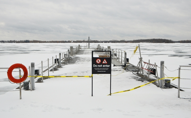 a danger do not enter sign and yellow caution tape across a dock on the waterfront, windswept snow, old railing,