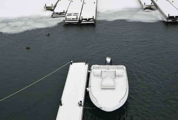 snow covered docks with one small snow covered boat, harbour, some ice and some open water