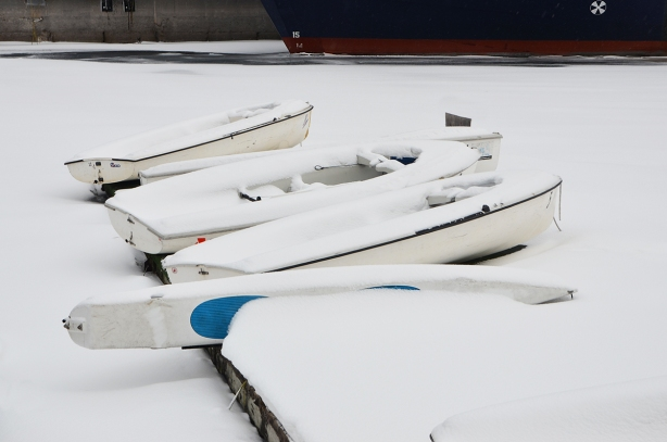 snow covered boats on snowy docks, bottom of larger boat is in the background.