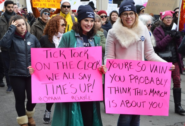 women marching in Womens march, holding pink signs