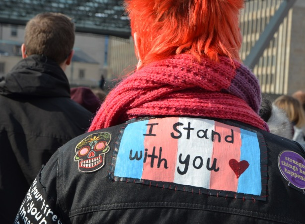 Womens March, Nathan Phillips square, from the back, a woman with short and very orange hair, has a patch on the back of her black jacket, rainbow flag with I Stand with you