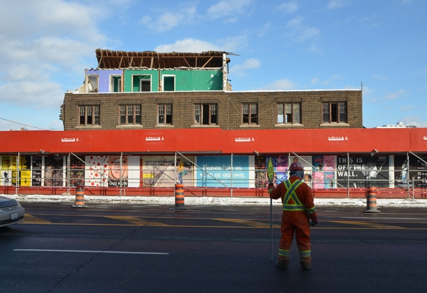 a construction worker in heavy winter orange clothes and yellow helmet, holds a stop sign to stop the traffic on Yonge street in front of a building being demolished