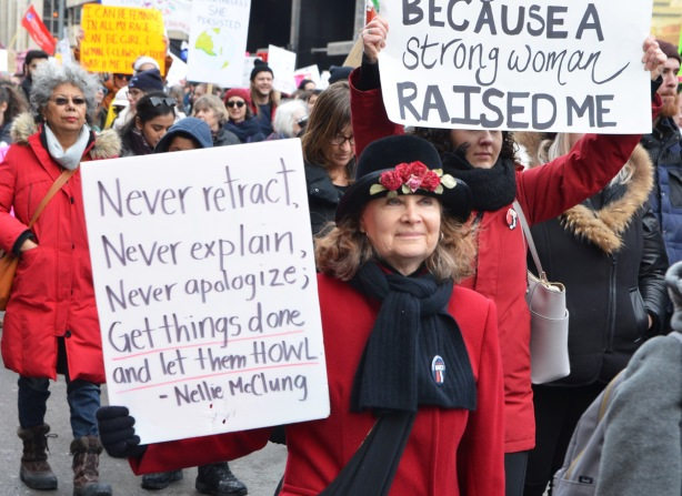 two protest signs, one says because a strong woman raised me. the other is a Nellie McClung quote about never retract, never explain, never apologize, get things done and let them howl