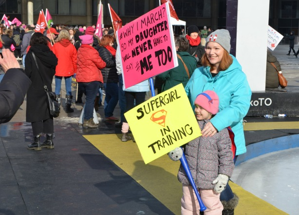 Womens March, Nathan Phillips square, by the rink a mother and daughter getting their picture taken. Both are holding signs, the daughter's sign is yellow and says Supergirl in training, mother's sign is pink and says