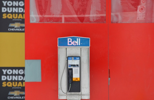 a Bell payphone in front of a red wall.