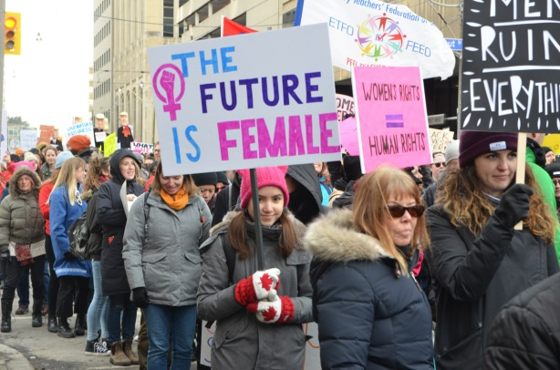 group walking in a protest march, the future is female is one of the signs being carried, walking on Dundas St