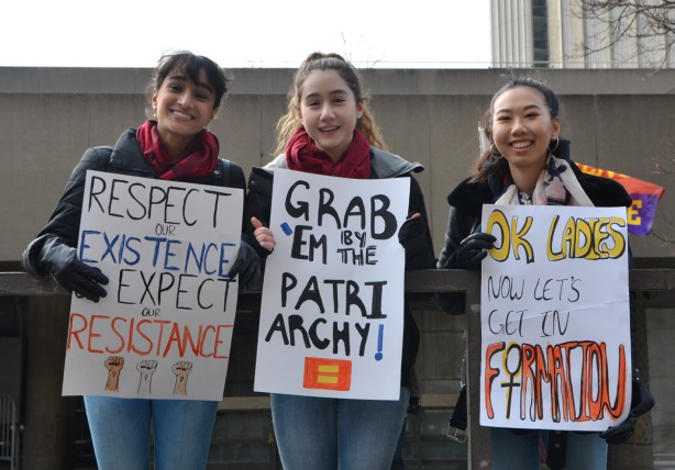 Womens March, Nathan Phillips square, 3 girls watch the protest march go by, they are each holding a sign - Respect my existence or expect resistance, the second is Grab 'em by the Patriarchy, and the third is OK with