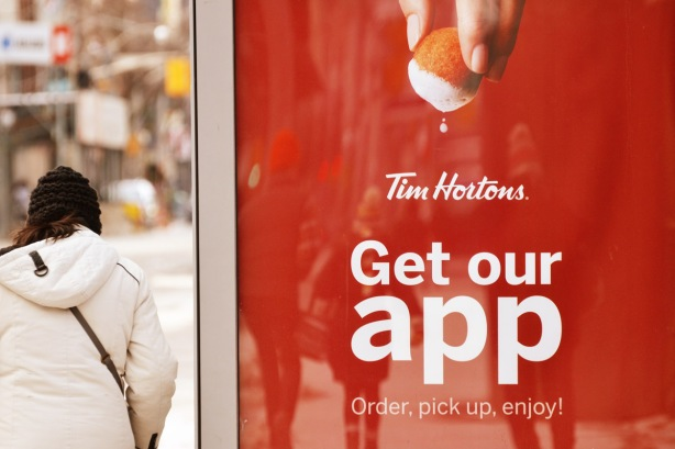 a tim horton's ad on the side of a bus shelter as a woman walks past, a timbit is being dunked into the foam of a latte