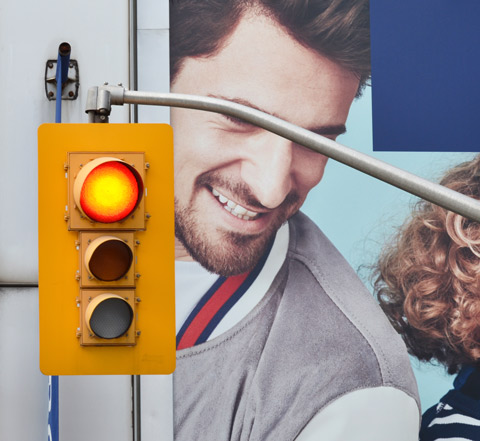 traffic signal, red light, in front of a billboard with a father and child